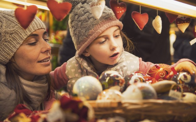mother and daughter selecting ornaments at christmas market