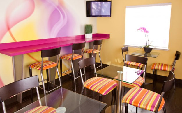 dining area contains small glass tables with 2 chairs and a wall of cafe bar seating. The room is decorated with bright wall paper, chairs and accents.