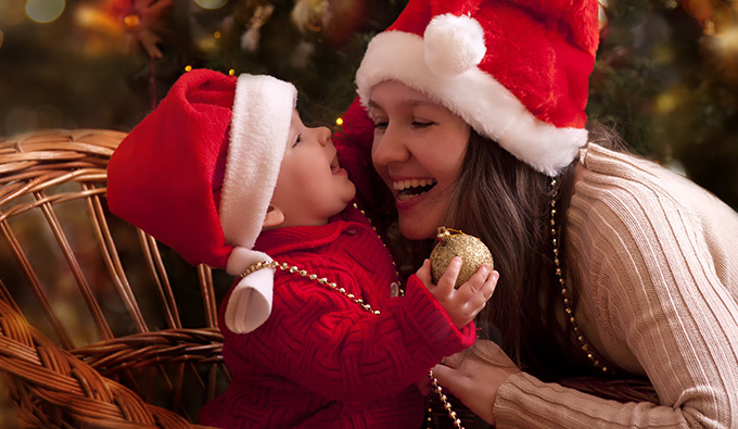 mom and infant child wearing santa hats sitting by a tree giggling