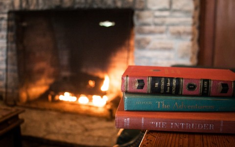 stack of books in front of a fireplace