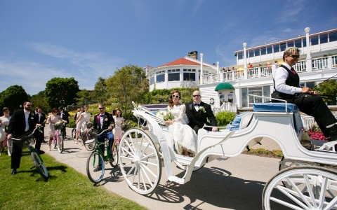 bride and groom riding in a horse drawn carriage
