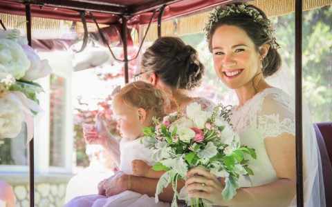 bride and bridesmaid sitting in a golf cart