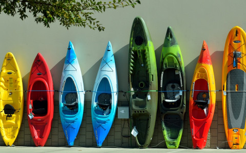 Eight kayaks of different colors propped against a wall
