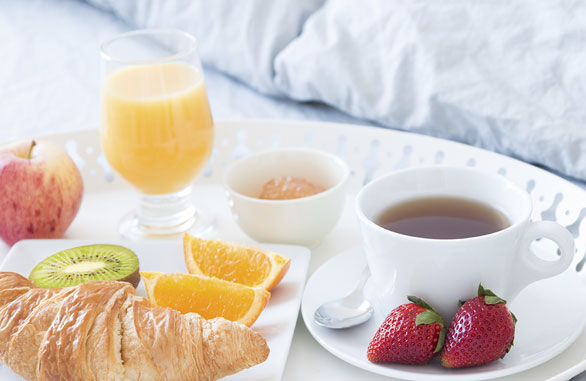 breakfast in bed with tea orange juice a croissant and fruit