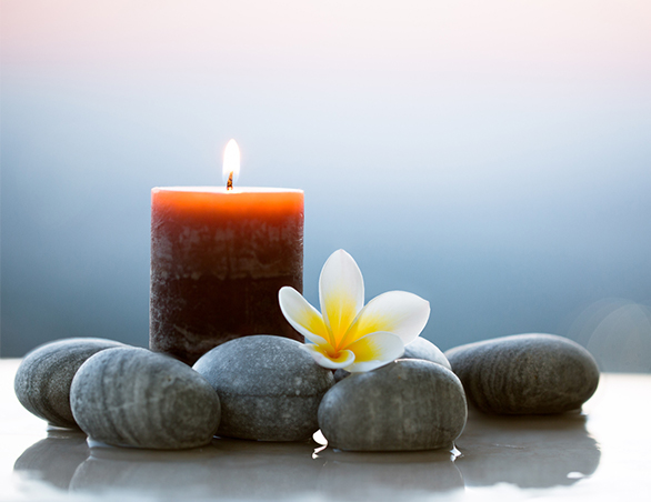 candle with rocks and flower