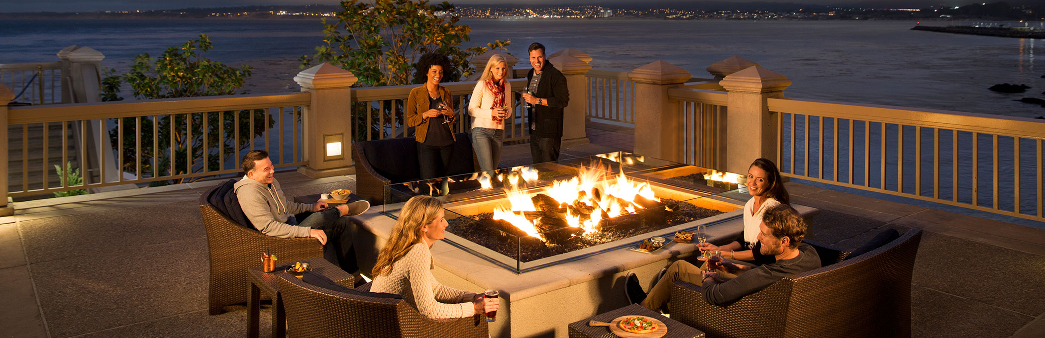 People around fire pit with ocean view