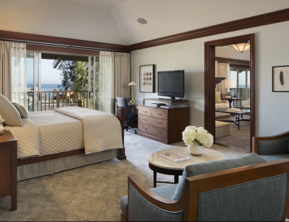 spacious bedroom with king bed and sliding glass door that overlooks the water