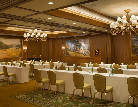 meeting room with two chandeliers and white rectangular tables with gold chairs