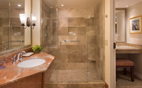 bathroom with granite countertop and marble shower