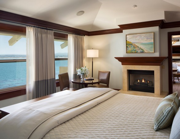 bedroom in the grand bay room with a king bed fireplace and large picture windows