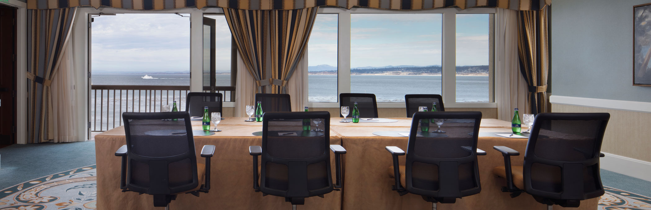 boardroom with open doors to the patio and view of the ocean