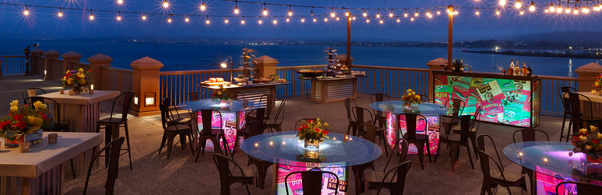 nighttime patio event with round tables, twinkle lights and black chairs