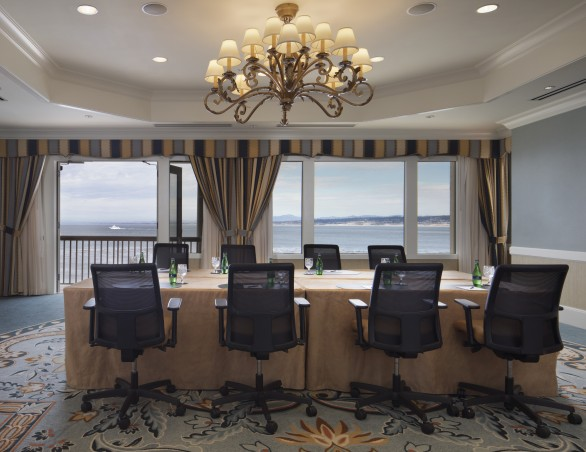 meeting room with a chandelier and brown rectangular table with black chairs