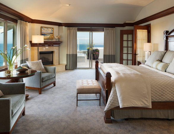 king bed and seating area with a view of the ocean in the presidential suite