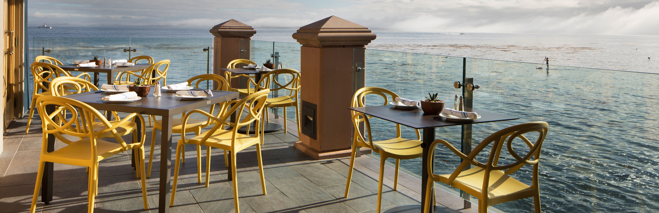 schooners outdoor patio with yellow chairs and a view of the water
