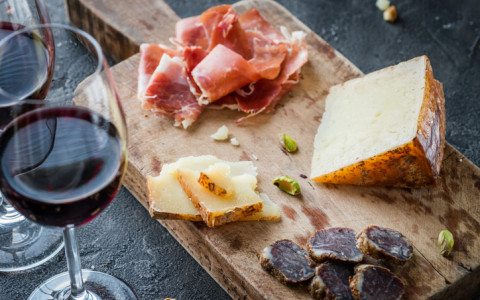 two glasses of red wine next to a wooden board of cheese and meat