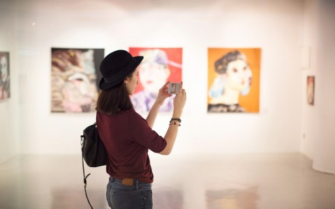 woman snapping a photo in art gallery