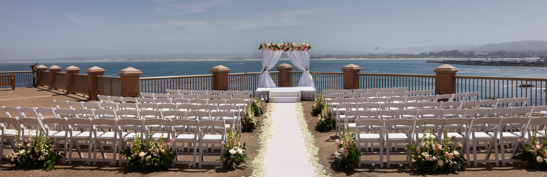 wedding ceremony overlooking the monterey bay with two sections of white chairs separated by a path of white rose pedals leading to a white curtain altar