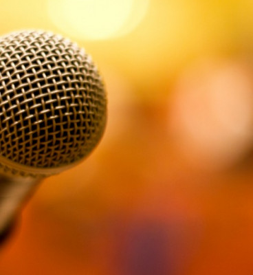 Close up of microphone with orange background
