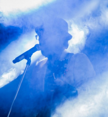 Musician at microphone obscured by smoke and blue strobe lights 59af304ed5abc 473x594