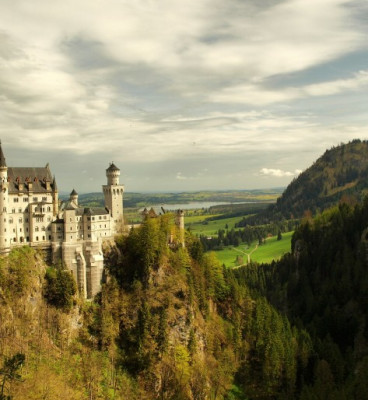 Neuschwanstein Castle and surrounding greenery of Alps beneath a cloud spattered sky 59da4eb6def3c 473x594