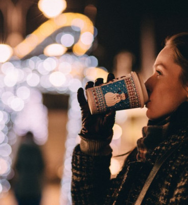 Woman dressed in scarf coat and gloves drinking coffee from holiday cup in front of illuminated Christmas display 2 5a033c7167e1e 473x594