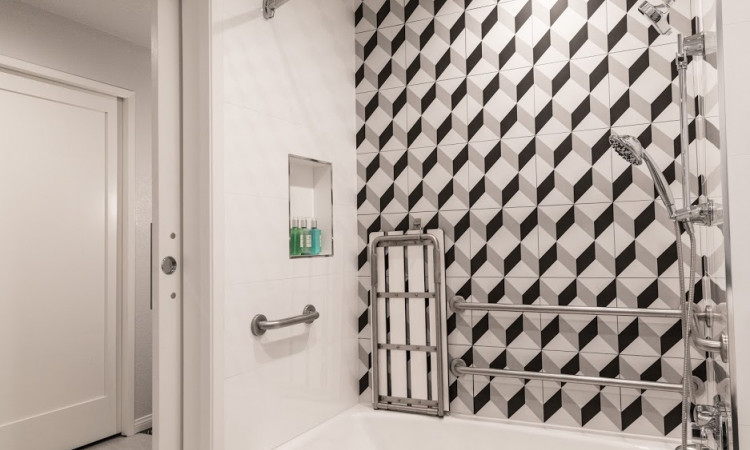 ADA Bathroom with a black and white tiled showed and grab bars