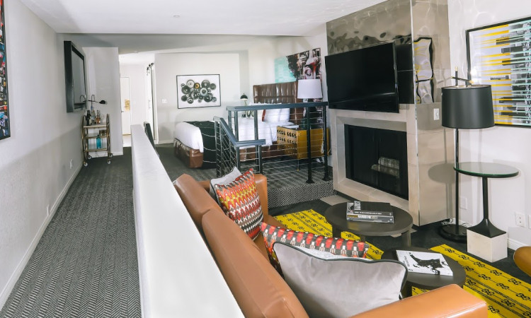 ADA King suite with brown leather couch fireplace with large tv seating and bedroom area