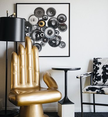 detail shot of a guestroom with the gold chair shaped like a hand in front of artwork made out of speakers