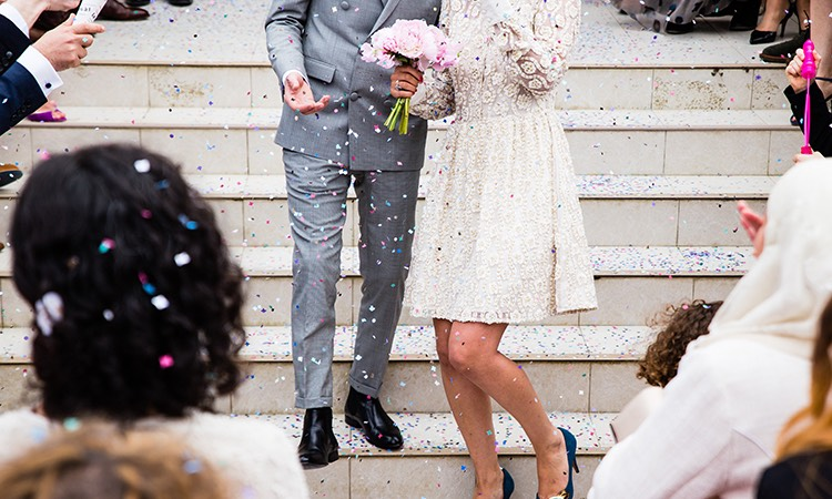 bride and groom coming down steps with confetti being thrown