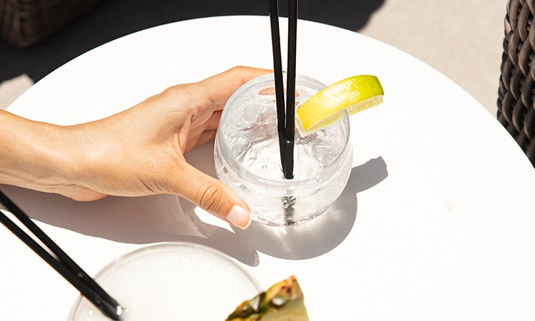 A Hand holding a cocktail with 2 black straws in the sunlight