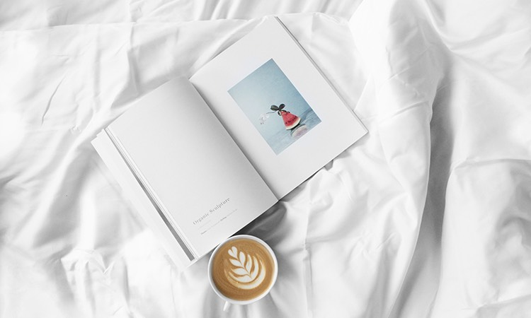 Cup of espresso on a bed with white linens and open book