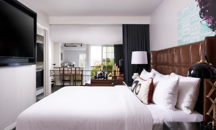 Guest room with king bed with white linens and leather headboard