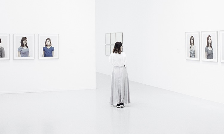 Woman walking around a stark white museum with portraits on the walls