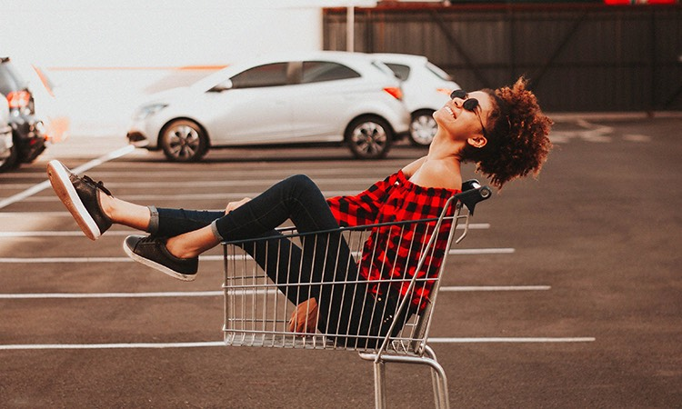 Trendy woman sitting in a shopping cart