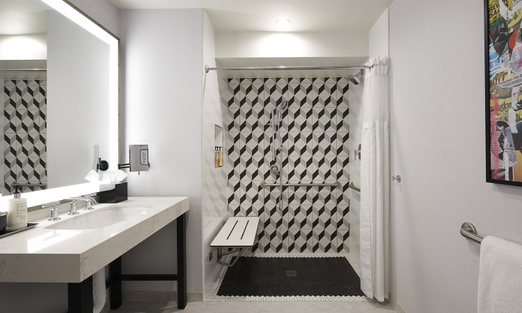 ADA bathroom with a black and white tiled shower with an ADA seat and grab bars