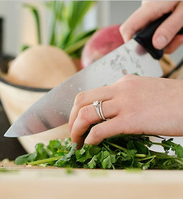 womans hands cutting up herbs on a wooden cutting board