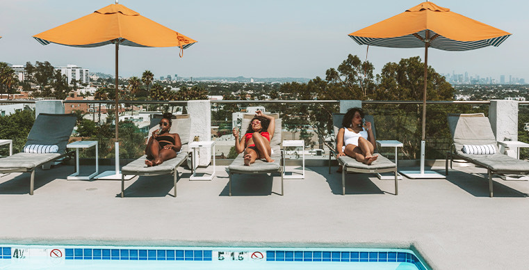 Three ladies lounging poolside on the rooftop