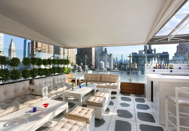 lounge area of rooftop bar with couches and low white tables