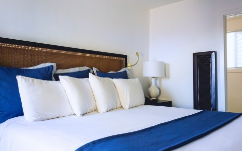 queen bed with crisp white sheets, navy blue accent pillows and blankets.