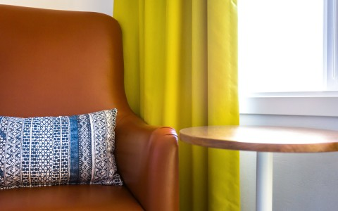 detail shot of large brown leather chair, side table and window with bright yellow curtains