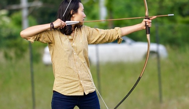 Female archer pulling back bow and arrow