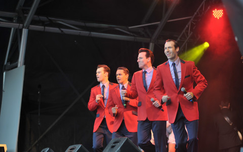 Cast of Jersey Boys in Red Sports coats dancing and singing on stage