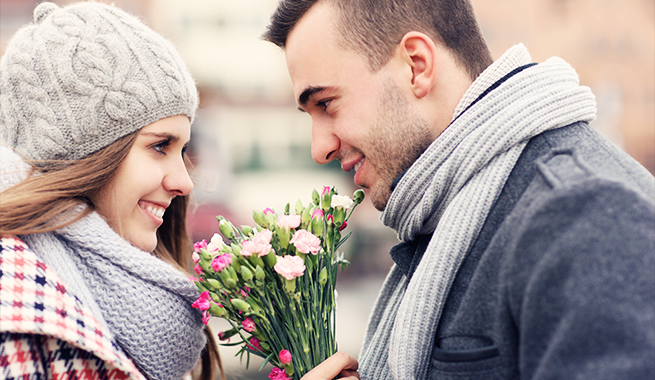 man and women in winter apparel looking in each others eyes while handing off a bouquet of flowers