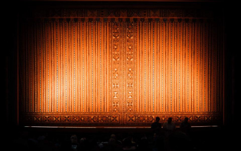 Orange curtain with light shining on it before the show starts