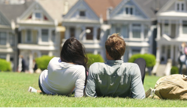 man and women sitting on grassy lawn  across from painted lady houses