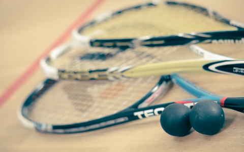 Three squash racquets and two squash balls on a squash court