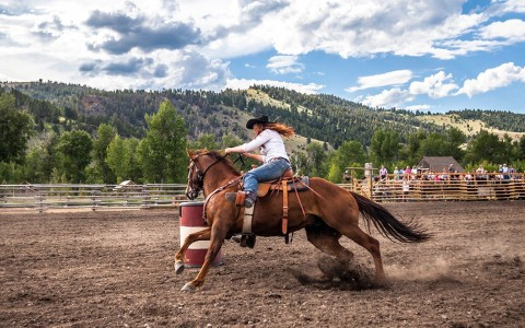female barrel racing on a horse in a dirt pasture in the mountains