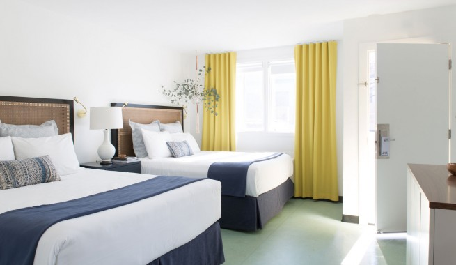 double room with 2 queen beds in room with crisp white sheets, navy blue accent pillows and blankets. 1 night stands. Bed adjacent to front door and window. Dress in front of beds