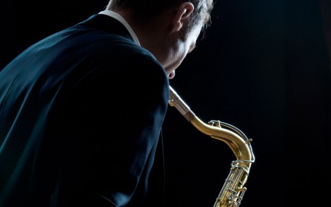 man in suit playing saxophone
